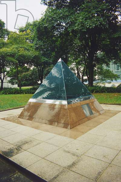 Singapore, Colonial Core, small glass-topped pyramid housing a time capsule which will be opened in 2015 to celebrate Singapore's Silver Jubilee, trees in background.