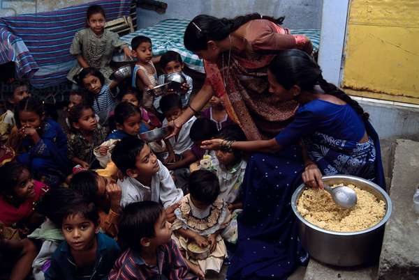 Young children are given cooked rice as supplementary food as a part of children's nutritional wellbeing, by CHETNA, a local NGO. Ahmedabad. Gujrat Province, India.  (photo)