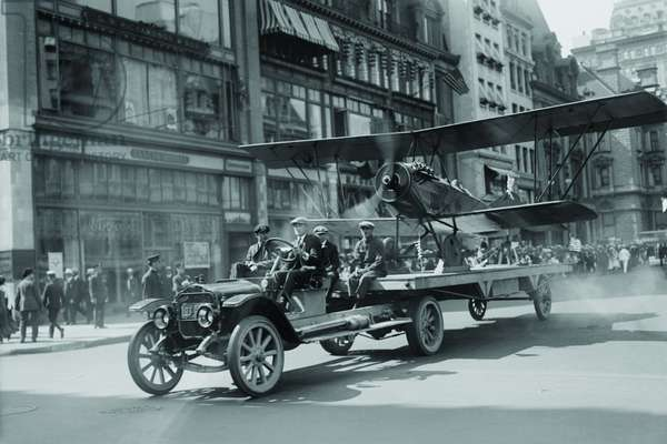 Biplane with spinning propeller is towed down Fifth Avenue New York for July 4th Parade (photo)