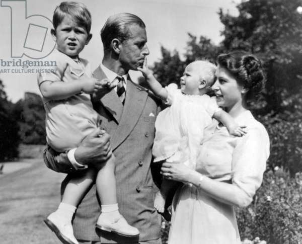Queen Elizabeth II and the Duke of Edinburgh, Prince Phillip holding Prince Charles and Princess Anne, 1952 (b/w photo)
