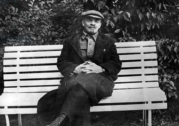 Vladimir Lenin seated on a bench.