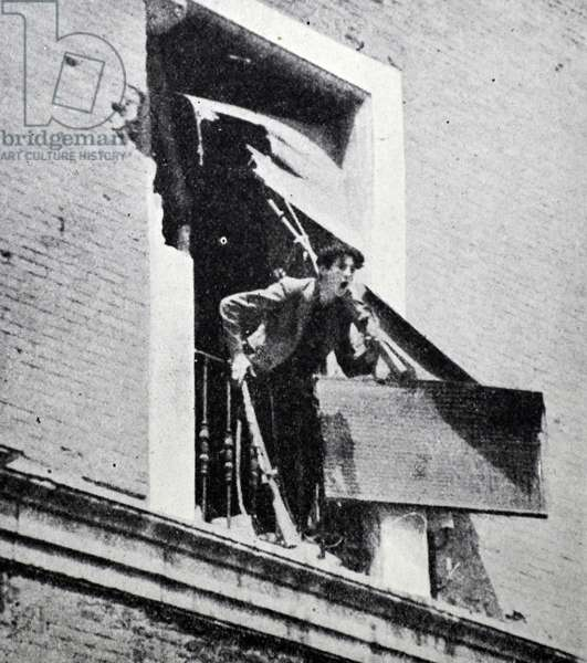 A republican soldier shouts to comrades below a window during battle in Barcelona, during the Spanish civil war 1938