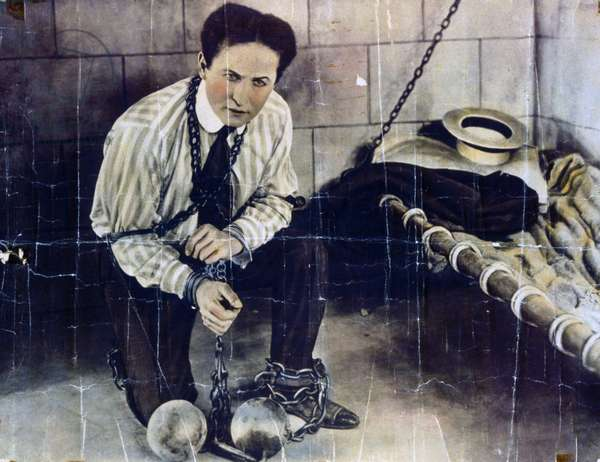 Photographic print, hand coloured, poster format, of Harry Houdini a Hungarian-American illusionist and stunt performer.