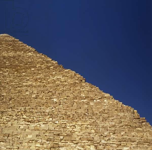 Egypt, Cairo, Giza, edge of a stone-block pyramid side against the sky.