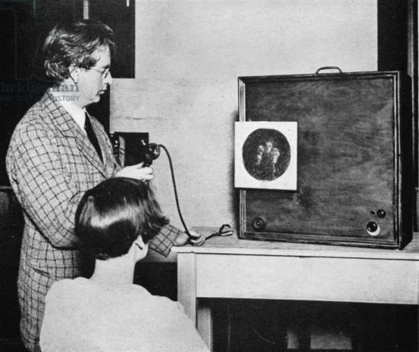 John Logie Baird (1888-1946) Scottish electrical engineer: pioneer of television. Baird in front of an early television ('Seeing by wireless') transmitter