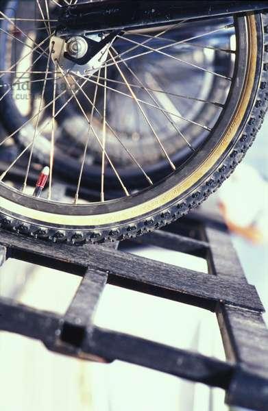 Close-up of a bike wheel on metal grating, UK