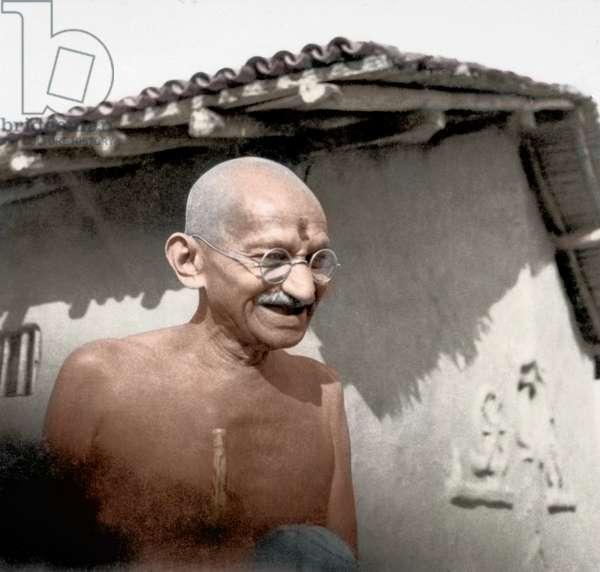 Mohandas Karamchand Gandhi dit Mahatma Gandhi (1869-1948), leader politique et spirituel indien, recevant une noix de coco devant sa maison a Satyagraha Ashram, janvier 1942 - Mahatma Gandhi receiving a coconut in front of his hut at Satyagraha Ashram, Sevagram, January 1942. ©Dinodia/Uig/Leemage