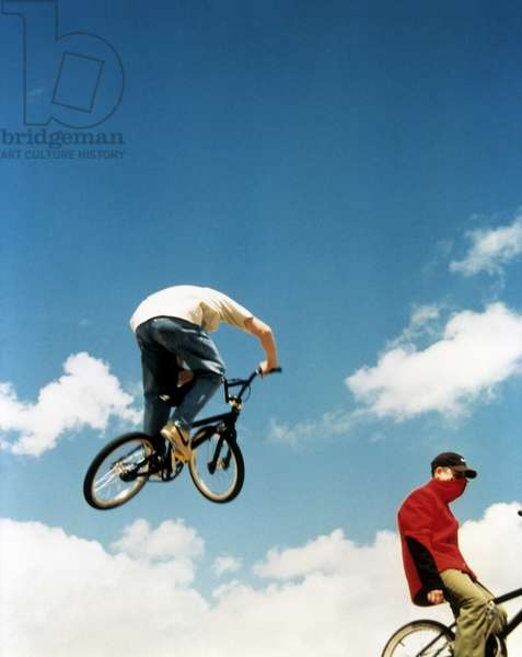 BMX rider catching some air while a biker below takes no notice, UK 2000's.