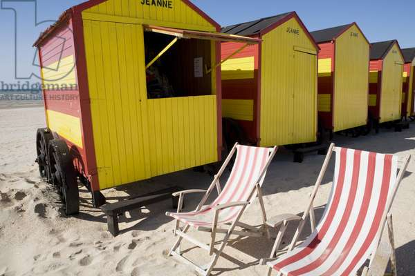 Belgium, De Panne, old fashioned brightly coloured beach huts and striped deckchairs on beach