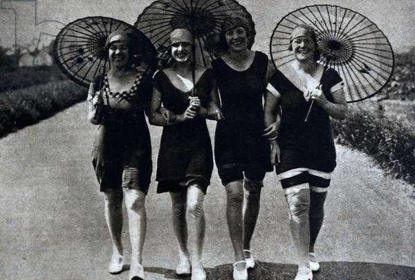 4 females are shown with umbrellas, at a beach party, 1926