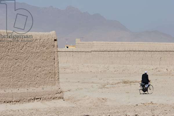 Man on A Bicycle and the Mud Walls of the Outskirts of Kabul, Afghanistan (photo)