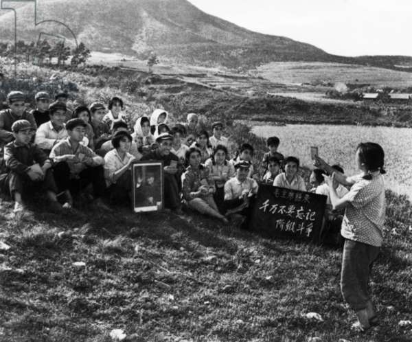During a Work Break, a Young Woman is Leading the Commune Workers in Singing a Song Praising Chairman Mao, Cultural Revolution, Tachai, Shansi Province, China, 1968.