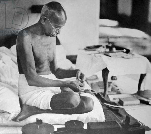 Mohandas Karamchand Gandhi spins cloth using traditional methods