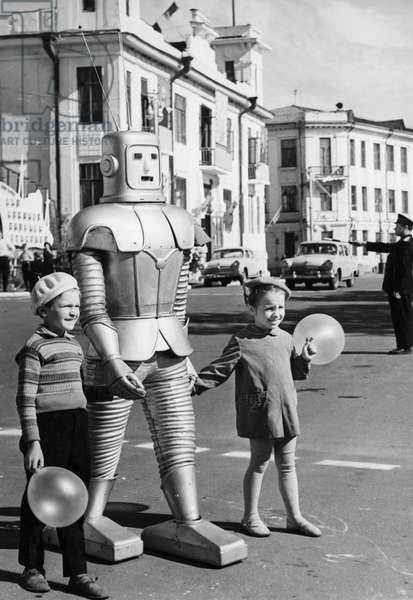 A Robot Belonging to Local Circus Performer Oleg Sokol Helping Two Children with Balloons Cross the Street in Arkhangelsk, USSR, 1967