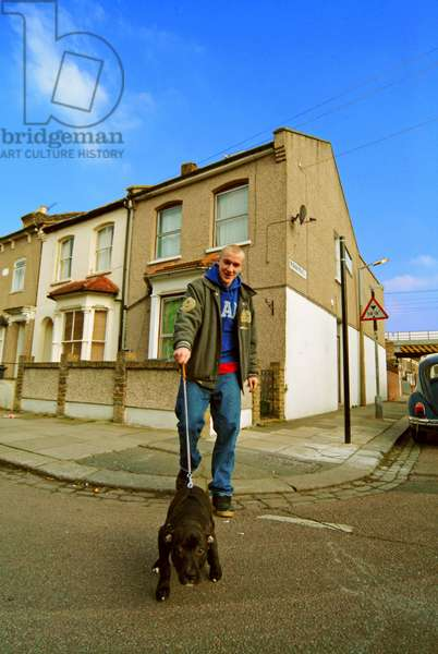 A youth walking his Pit Bull Terrier dog in the street, London UK 2006.