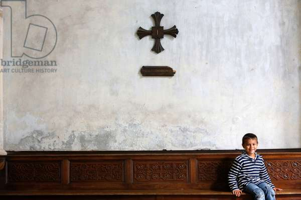 Boy in a catholic church (photo)