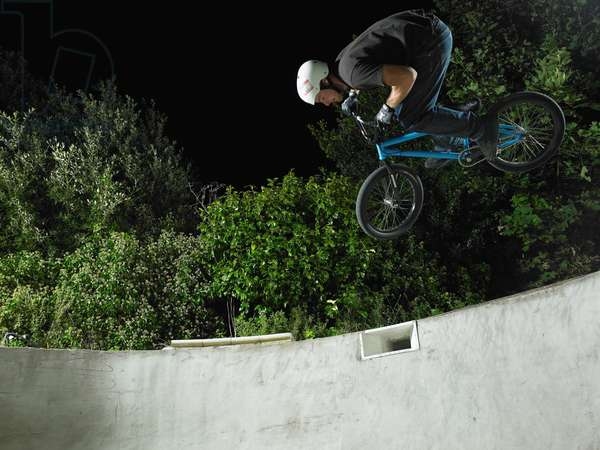 Man on a blue bmx getting air in a backyard pool at night, UK