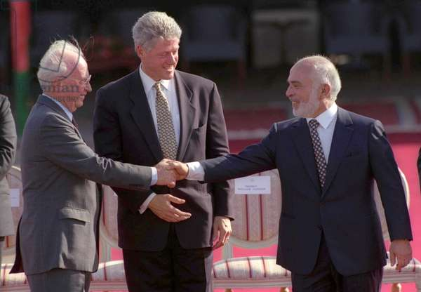 The Israel–Jordan peace treaty being signed in 1994. US President Bill Clinton watches Jordan's King Hussein and Israeli Prime Minister Yitzhak Rabin sign the treaty on the White house lawn