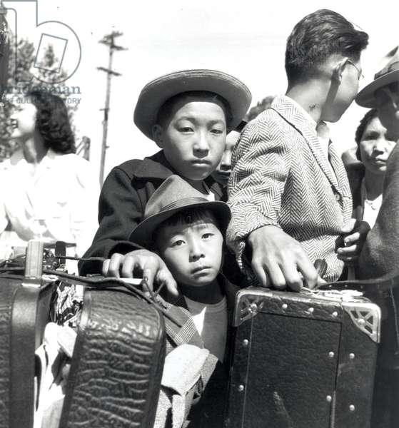 Young Japanese Americans internees in a baggage inspection line, Turlock, California, 2nd May 1942 (b/w photo)