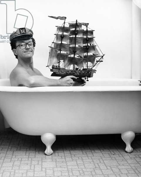 Man in captain hat holding toy ship in bathtub (b/w photo)