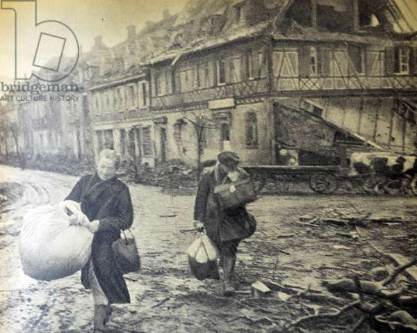 World War two : French civilians in Cernay struggle with baggage across the war damaged streets of the town