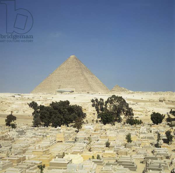 Egypt, Cairo, Giza, modern Muslim cemetery built by the 'Great Pyramid', seen in the background.