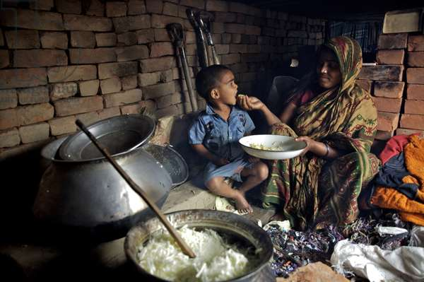 A woman feeds her child while cooking for laborers using garment factory wastes as fuel, in one of the makeshift brick housing, at the living quarters of a brick factory, in Jodeypur, on the outskirts of Dhaka, Bangladesh. Women and children of all age do all sorts of work in brick factories including carrying fresh molded bricks, sorting coals and cleaning. Most of them earn just enough to be able to have three basic meals everyday. February 14, 2007.  (photo)