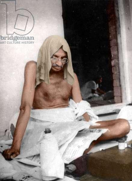 Mohandas Karamchand Gandhi dit Mahatma Gandhi (1869-1948), leader politique et spirituel indien, lisant, sa tete et sa bouteille sont couverte en protection de la chaleur ,vers 1940 - Mahatma Gandhi reading, c. 1940. Head and bottle carry wet cloths in order to protect from heat. ©Dinodia/Uig/Leemage