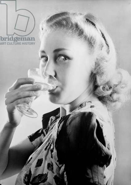 Woman drinking a glass of champagne, 1949 A photograph of a woman drinking a glass of champagne, taken by Photographic Advertising Limited in 1949