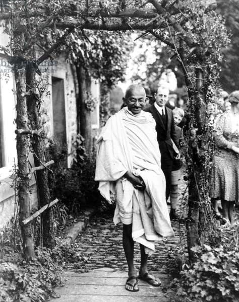 Mahatma Gandhi posing under a rustic arch, England, 1931