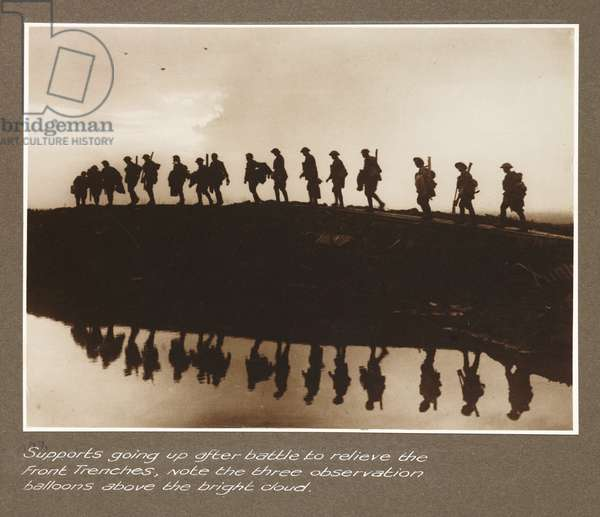 Premiere guerre mondiale: troupes de renfort avancant vers les tranchees du front, avec trois ballons d'observation dans les nuages