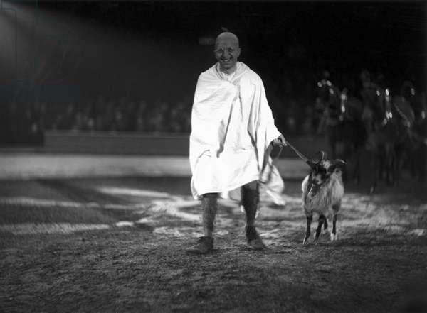 """Mahatma Gandhi"" leading a goat around a circus ring"", annees 1930"