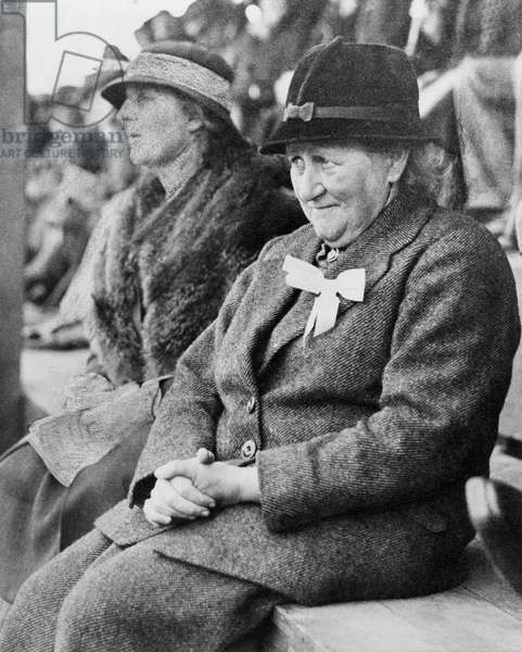 Beatrix Potter sitting on a bench at the Keswick Show, of which she was President, September 1935 (b/w photo)