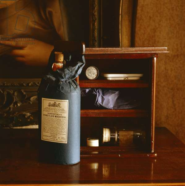 A bottle of Milk of Magnesia wrapped in blue paper with a small cabinet behind, from Walter's Bedroom (photo)