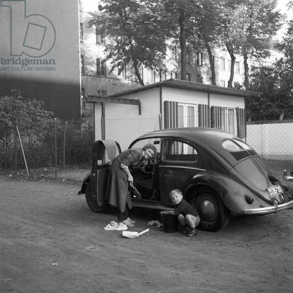 Popular Volkswagen beetle being washed by the family, Hamburg 1954