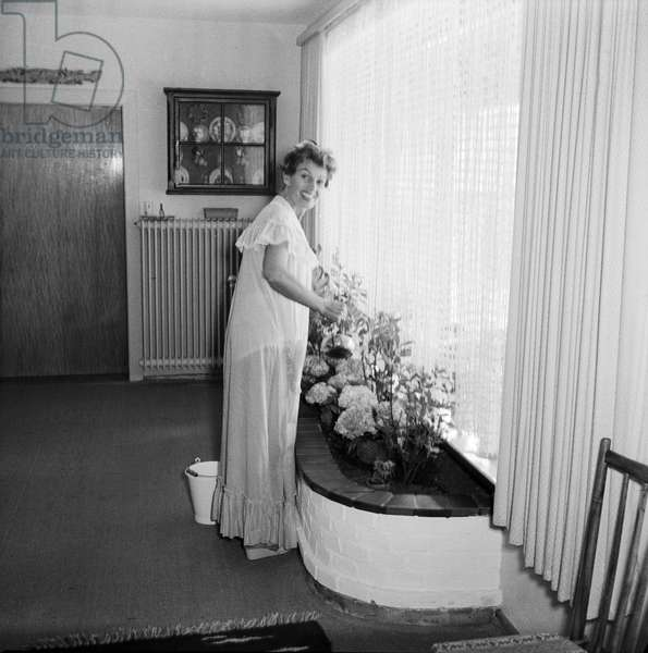 German singer and actress Lale Andersen watering the flowers at her house, called Sonnenhof, on the East Frisian island Langeoog, mid 1957