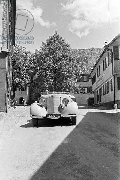 Travellers driving through the town Alpirsbach in the Black Forest, Germany 1930s (b/w photo)