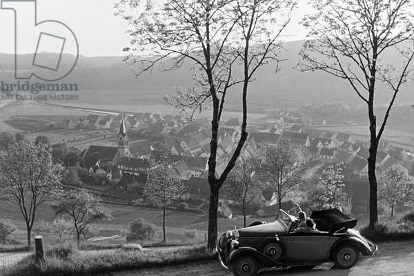 Two young women making a trip with a convertible trough the little villages of the Black Forest, Germany 1930s (b/w photo)