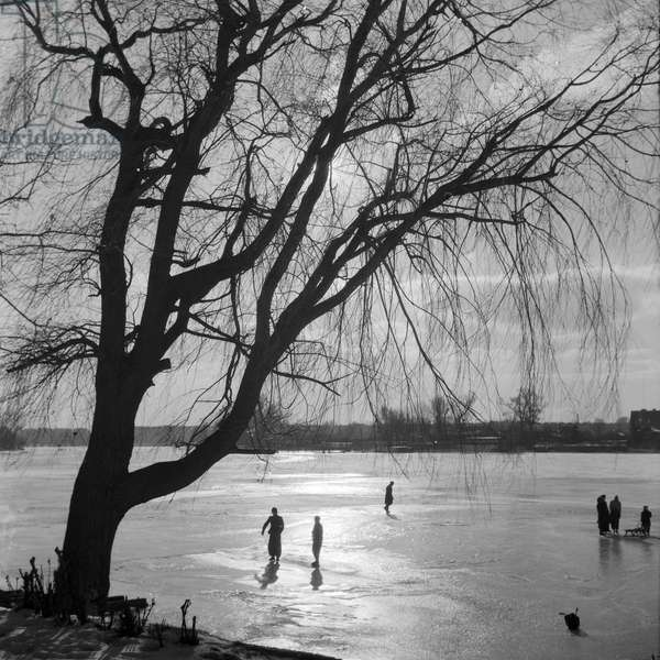 People ice skating on a frozen over lake, Germany 1930s (b/w photo)