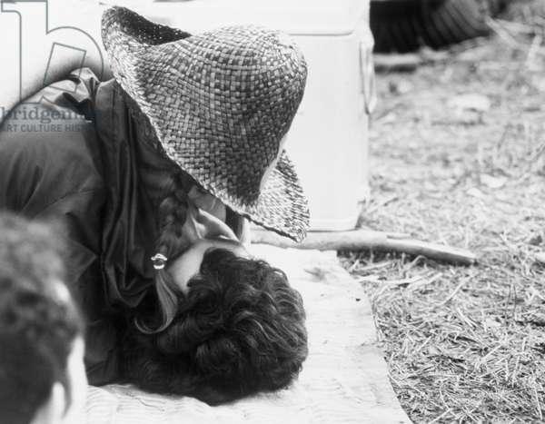 """Couple s'embrassant, la jeune femme est coiffee d'un chapeau de paille. Scene tiree du Film documentaire """"""""Woodstock"""""""" de Michael Wadleigh tourne lors du festival de musique, emblematique du mouvement hippie, qui eut lieu entre le 15 et le 18 aout 1969."""