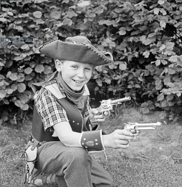 A boy dressed as a cowboy dog in the garden, Germany 1960s