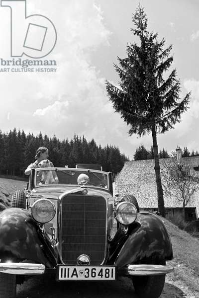 A young woman and her dog on a trip with a convertible on the hill Brend in the Black Forest, Germany 1930s (b/w photo)