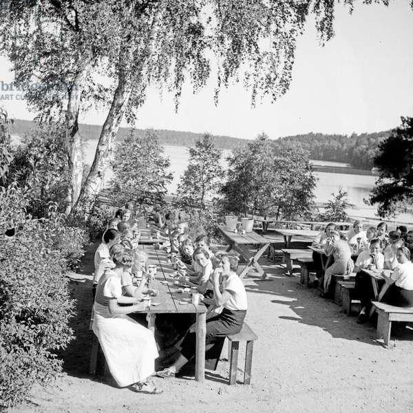 Having dinner at the leisure camp of the Deutsche Arbeitsfront at Altenhof, Werbellinsee, Brandenburg, 1930s (b/w photo)