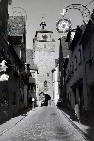 The way to the White Tower is passing by many appealing taverns with decorated shutters, Rothenburg ob der Tauber, Germany 1930s (b/w photo)