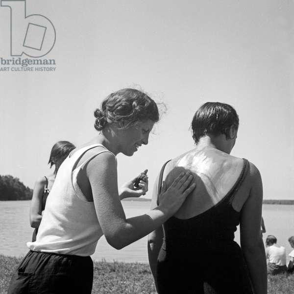 Applying suntan lotion is the best rescue against sunburn at the leisure camp of the Deutsche Arbeitsfront at Altenhof, Brandenburg, 1930s (b/w photo)
