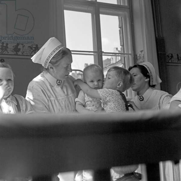Two sisters with children of the Red Cross hospital children medical unit at Munich, Germany 1930s (b/w photo)