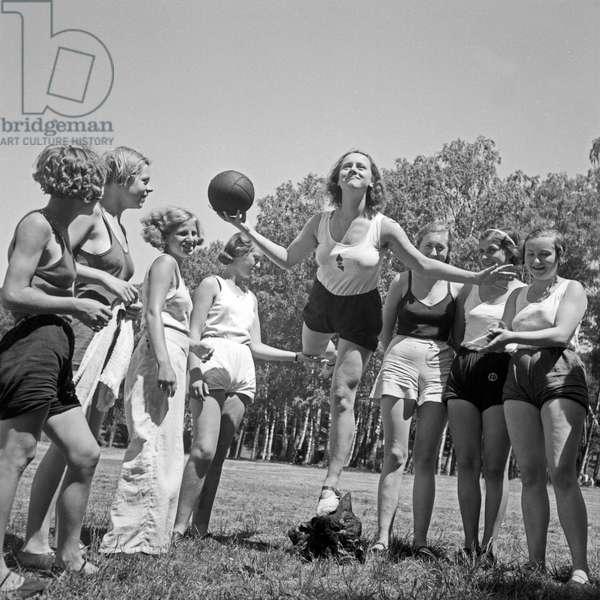 Girls doing gymnastics with a ball at the leisure camp of the Deutsche Arbeitsfront in Altenhof, Brandenburg, 1930s (b/w photo)