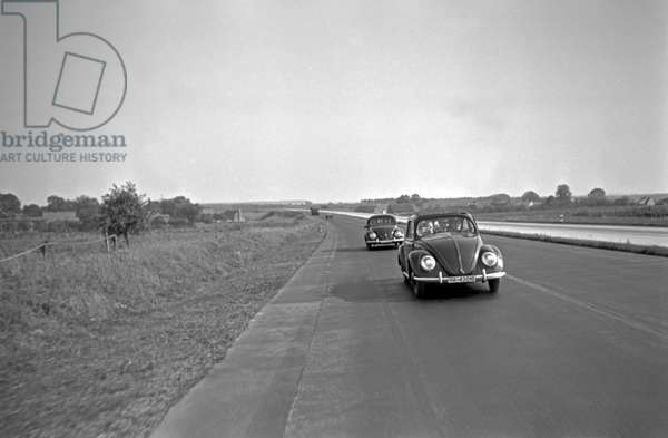 Two model of the Volkswagen beetle, or KdF car, with open and closed roof on the test track near Wolfsburg, Germany 1930s (b/w photo)