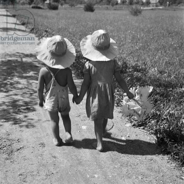 Two toddlers strolling through summer, Germany 1930s (b/w photo)