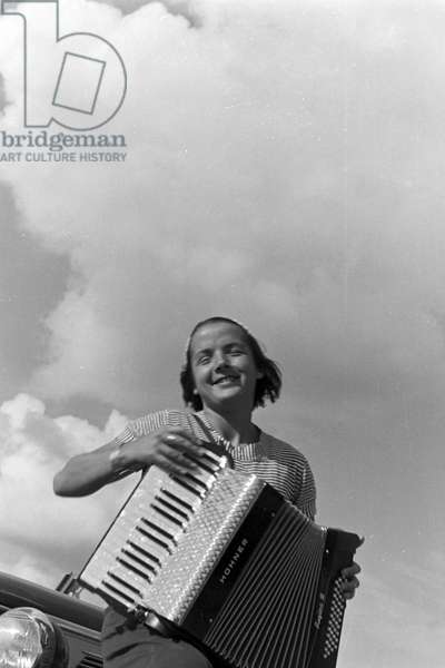 A young woman playing the harmonica, Germany 1930s (b/w photo)